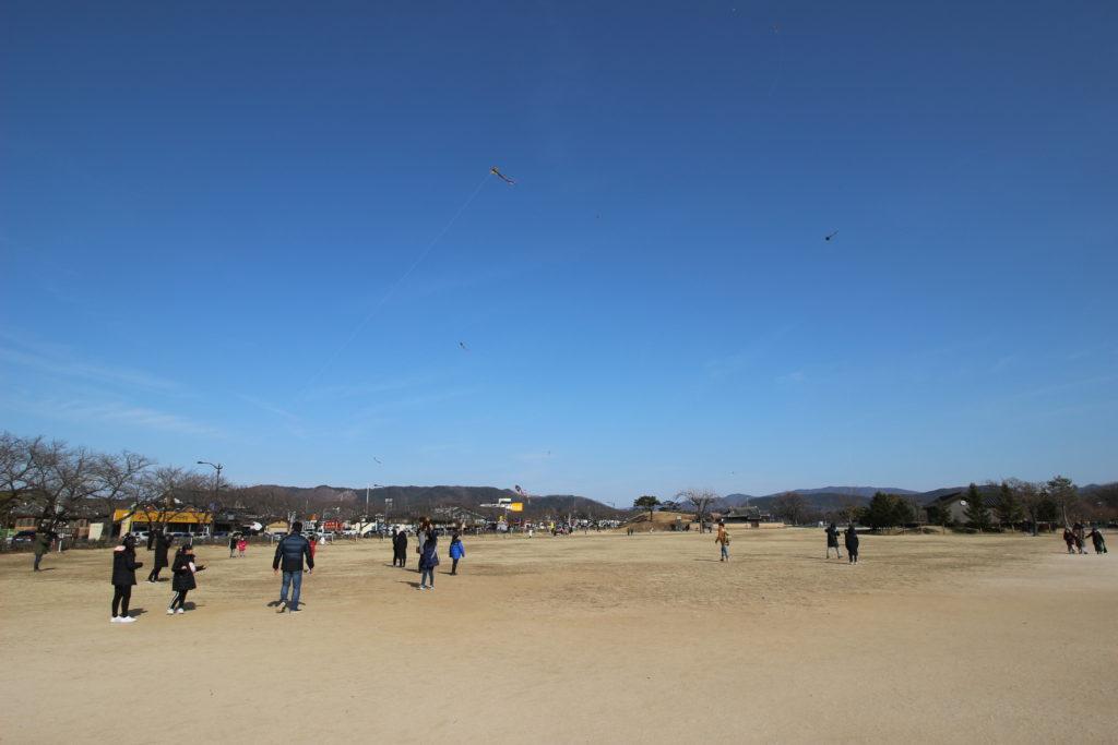 広場で凧揚げをする人たち