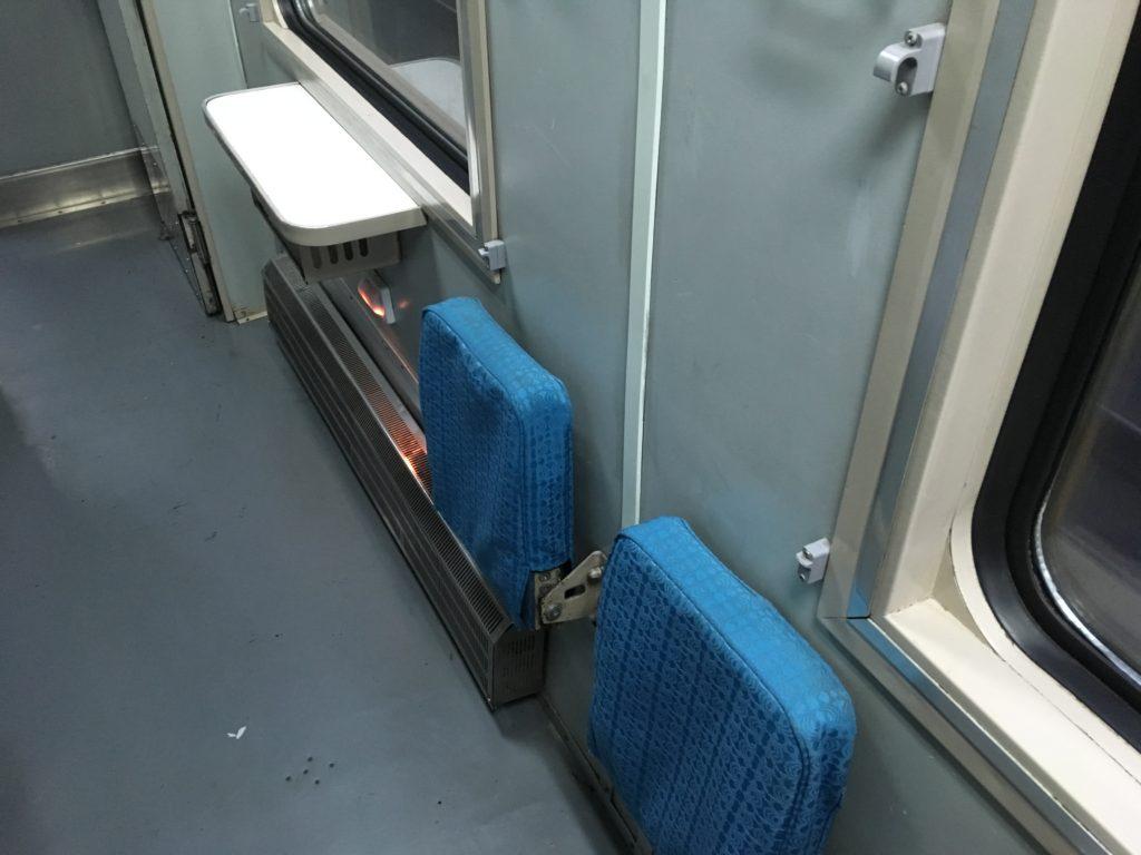 通路に設置されている小さい机と折りたたみ式の椅子です