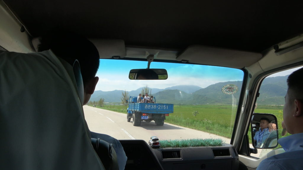 トラックの荷台に乗って移動する人たち
